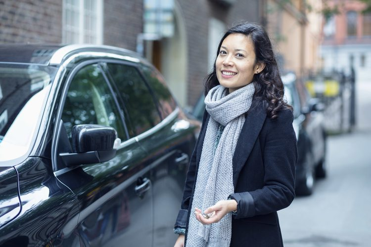 Happy woman beside a parked car on street