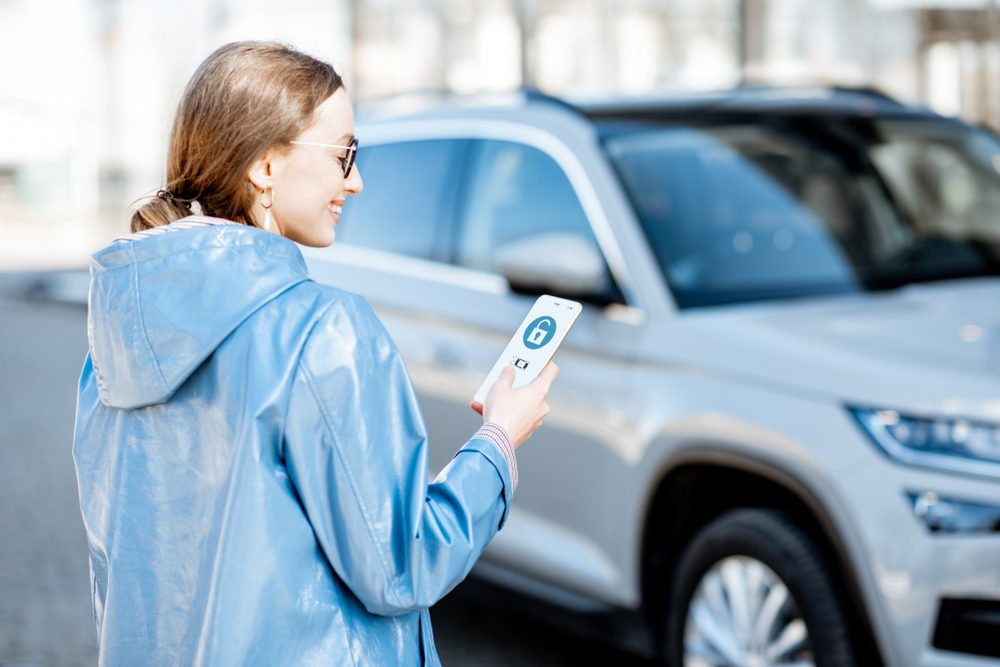 Connected Car Essentials - woman unlocking car with a smartphone